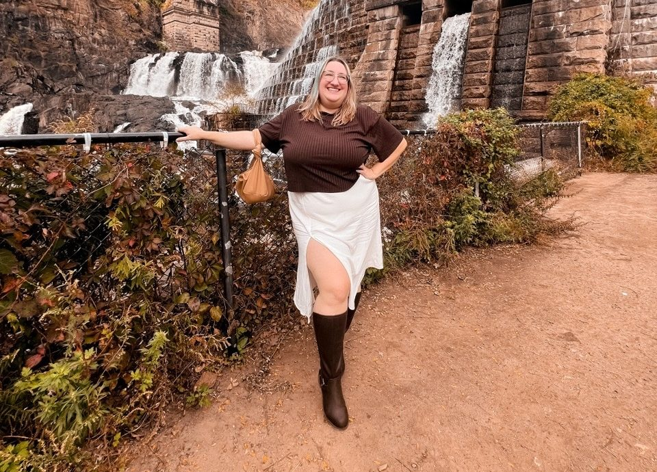 Sarah stands in front of a waterfall under a bridge wearing a brown cropped tee, a white midi skirt with a slit over the left thigh, and brown riding boots